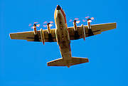 White propellor plane on blue sky background coming in to land