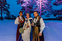 Two  female guests at a Norwegian wedding wearing the bunad, the Norwegian National Costume, stand with the bride before the reception, Trysil, Norway.