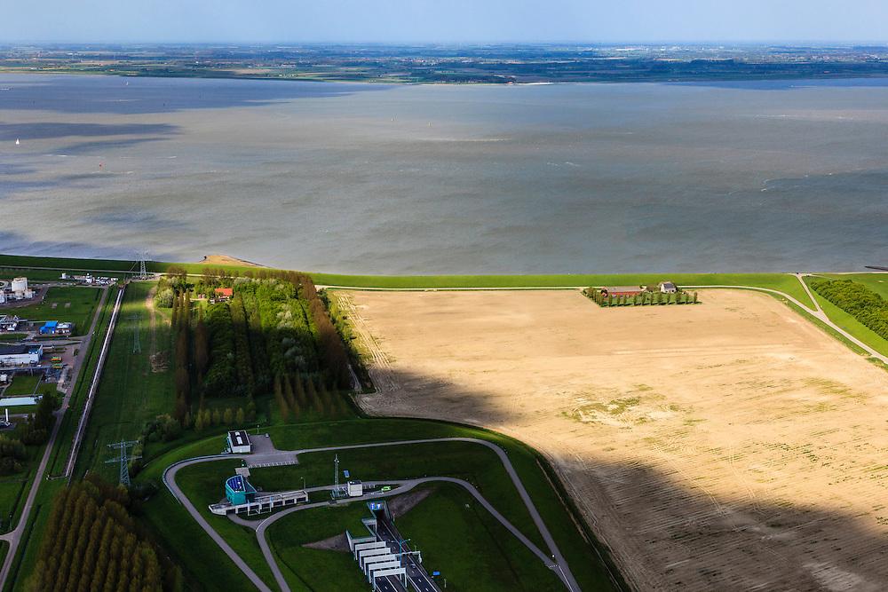 Nederland, Zeeland, Terneuzen, 09-05-2013; Zeeuws-Vlaanderen, Terneuzen, zuidelijk ingang van de Westerscheldetunnel (midden beneden in beeld). Westerschelde en Zuid-Beveland aan de horizon. Boerderij aan het water op een kale akker.<br /> Tunnel entrance (bottom, m) of the tunnel in the Westerschelde, connecting Zeeuws-Vlaanderen and Zuid-Beveland (on the horizon) in the province of Zeeland.<br /> luchtfoto (toeslag op standard tarieven);<br /> aerial photo (additional fee required);<br /> copyright foto/photo Siebe Swart.