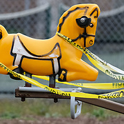Caution tape is strewn on a playground horse ride at Library Park in Maumee, Ohio, on Monday, April 27, 2020. Playground equipment has been off limits due to concerns of COVID-19 spread. THE BLADE/KURT STEISS