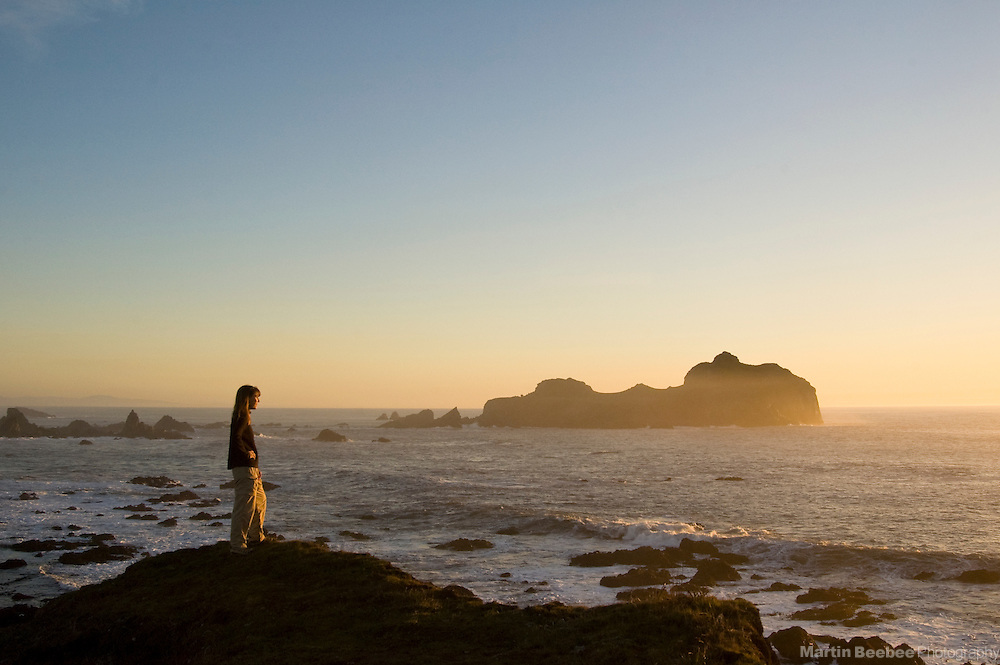 A woman stands on a coastal bluff at sunset with Castle Rock National Wildlife Refuge in the background, near Crescent City, California