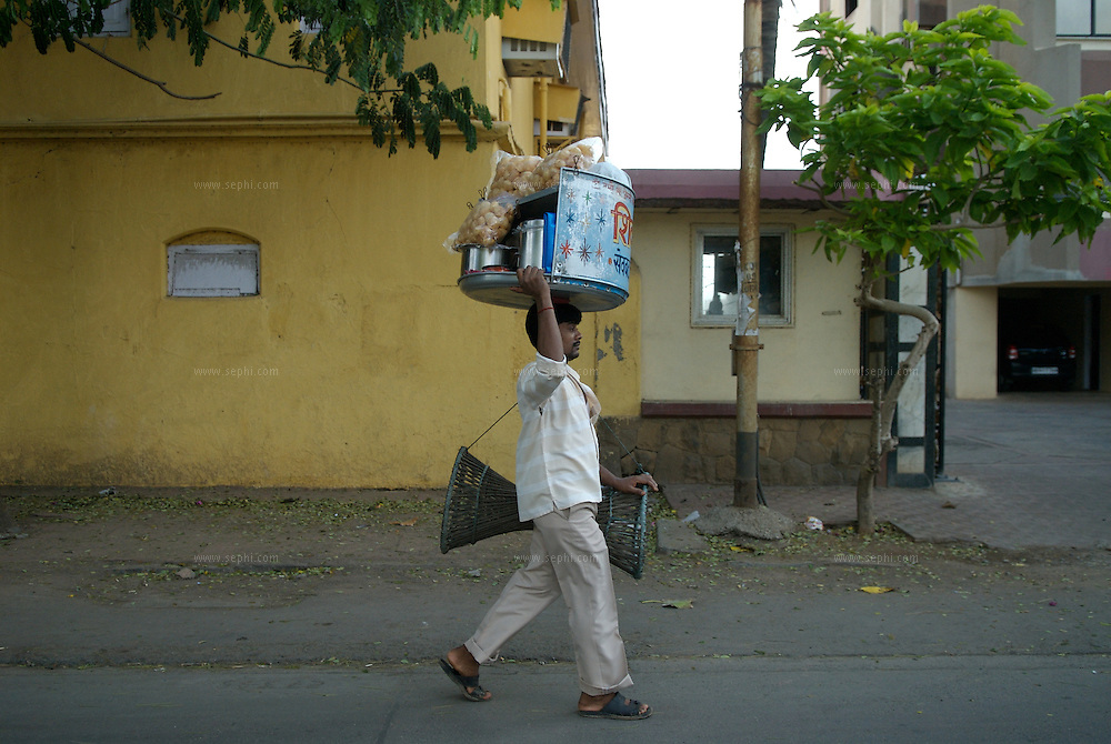 A vendor carries a tray of golgappa, or panipuri, on his head and a cain chair on his arm on way to the location where he will put up his stand for the evening. Panipuri, or Pani puri, is a snack synonymous with the beaches of Mumbai. However, it is also very popular in all other parts known by many names like golgappa (plural golguppe) in North India, Foochka (Puchka) in West Bengal, Gupchup in some central parts of India like Hyderabad. Mumbai, March 2006