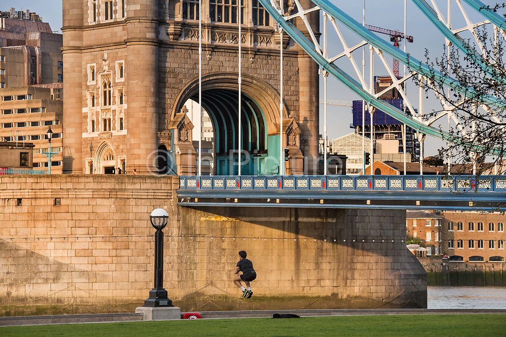 Keeping fit during the lockdown by Tower Bridge at 6pm on 9th April 2020 in London, United Kingdom. Normally crowded with people leaving work the City of London is like a ghost town as workers stay home during the Coronavirus pandemic.