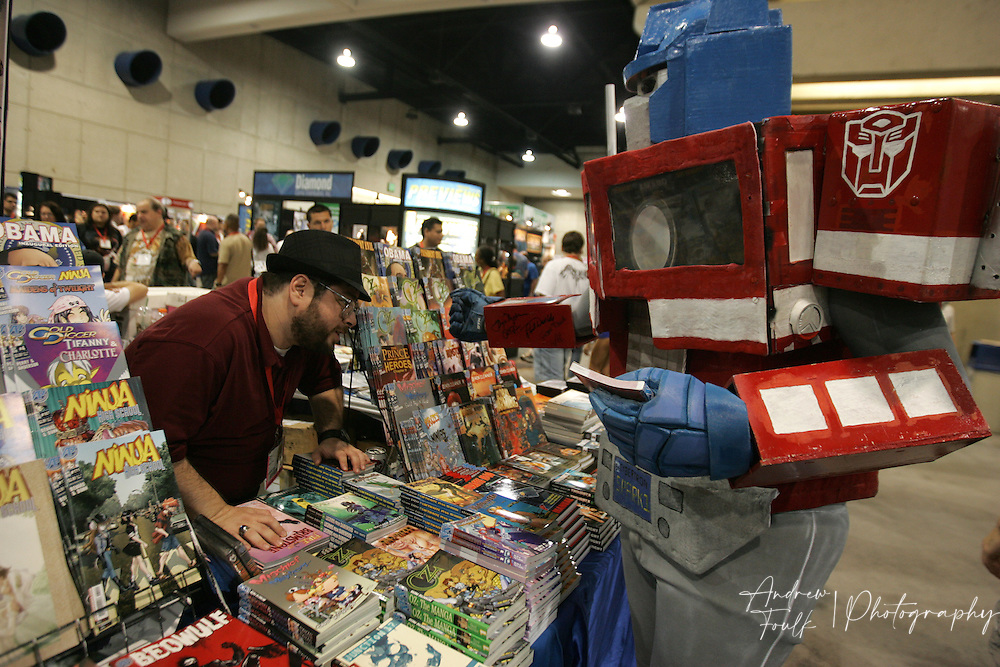 """Andrew Foulk/ Zuma Press.July 23, 2009, San Diego, California, USA.  Comic Con.  A Comic Con vendor takes a look at the autographs """"Optimus Prime"""" got on his arm , during day one of the 40th annual San Diego International Comic Con."""