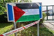 """Leicester, United Kingdom, May 19, 2021: A tape says """"War Crimes Scene"""" placed by the Palestine Action activists who climbed on the rooftop of the Elbit Systems manufacturer in Leicester. People gathered to support UK based Pro-Palestinian activists group """"Palestine Action"""" who seized control of the Leicester based factory of Elbit subsidiary UAV Tactical Systems on Wednesday, May 19, 2021. Activists say that """"the occupation is aiming to be as disruptive as possible; these activists are determined to prevent Elbit from resuming its business of bloodshed."""" (Photo by Vudi Xhymshiti/VXP)"""