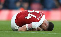Arsenal's Granit Xhaka (left) lays on the floor injured