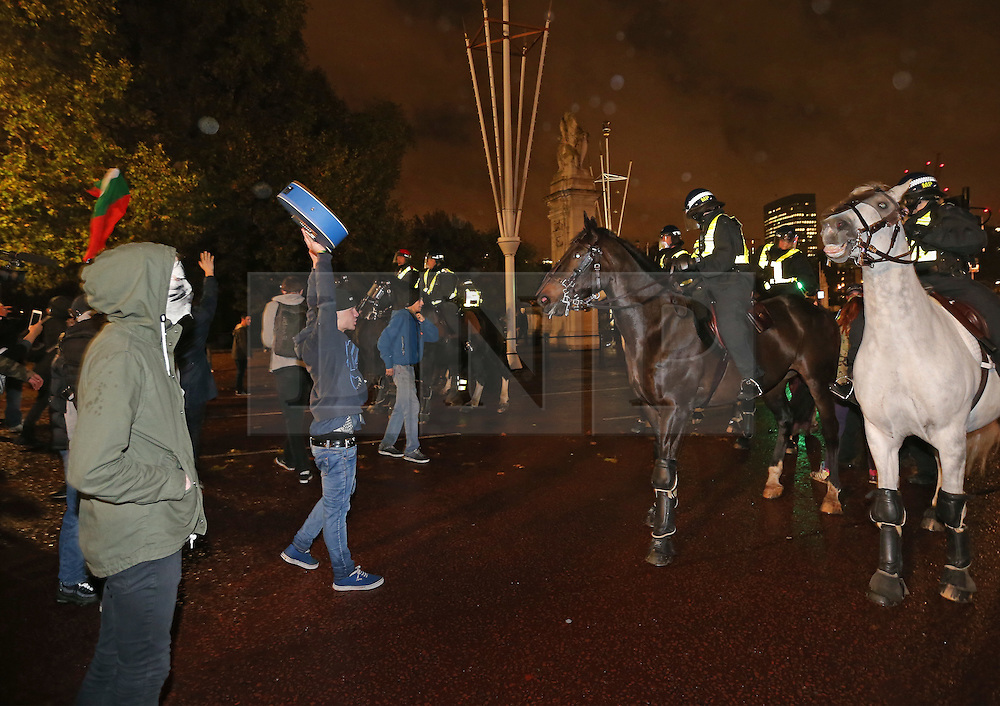 © Licensed to London News Pictures. 05/11/2015. London, UK.  Anti-capitalist protestors face mounted police in The Mall near Buckingham Palace during the Million Mask march. Photo credit: Peter Macdiarmid/LNP