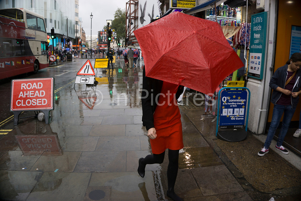London, UK. Sunday 23rd August 2015. Heavy summer rain showers in the West End. People brave the wet weather armed with umbrellas and waterproof clothing. Leicester Square.