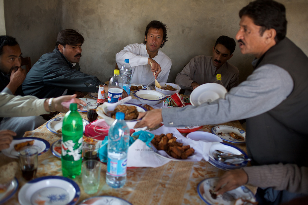 Imran Khan and members of his polical party Tehrik-e-insaaf have lunch with contractors on the site of a Namal college funded by Khan and other donators. The college has been established by Khan to promote education in his constituency. Khan will be using his Chancellorship of Bradford University in the UK to foster ties between the two institutions. Khan established a cancer hospital in Karachi in 1994 the success of which he hopes to emulate at Namal college. <br /> <br /> Cricketer Imran Khan made his Test debut against England in 1971. He became captain of the Pakistan team in 1982 and lead them to World Cup victory in 1992 after which he retired.<br /> <br /> Imran Khan established the Tehrik-e-insaaf (or Moverment for Justice) in 1996. Through Tehrik-e-insaaf, Khan has demanded that the Pakistan government make institutional reforms to address corruption and end the present dictatorship. Khan would like a more equitable distribution of resources in Pakistan, the granting key civil liberties and an increas in public service spending. He is particularly scathing of the relationship between President Musharraf and US President Bush.<br /> <br /> Imran Khan became a Member of the Pakistani Parliament for Mianwali, Panjab, in the October 2002 elections.<br /> <br /> Photo: Tom Pietrasik<br /> Panjab, Pakistan<br /> 28th January 2006
