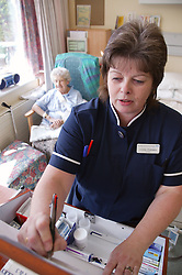 Nurse with disability administering medication from drugs trolley in hospital,