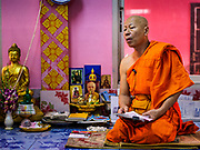 """30 DECEMBER 2017 - BANG KRUAI, NONTHABURI, THAILAND:  A Buddhist monk leads a prayer during a resurrection ceremony at Wat Ta Khien, about 45 minutes from Bangkok in Nonthaburi province. The temple is famous for the """"floating market"""" on the canal that runs past the temple and for the """"resurrection ceremonies"""" conducted by monks at the temple.      PHOTO BY JACK KURTZ"""