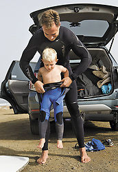 Aug. 29, 2013 - Morro Bay, CA, USA - Triston Gailey, 3, gets some help squeezing into his wetsuit from his dad Todd before hitting the waves in Morro Bay, California, August 29, 2013. (Credit Image: © Joe Johnston/TNS/ZUMAPRESS.com)