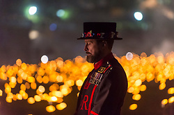 "© Licensed to London News Pictures. 05/11/2018. LONDON, UK. A Yeoman Warder stands amongst lit flames.  A new installation by designer Tom Piper called ""Beyond the Deepening Shadow: The Tower Remembers"", is now open for the public to view at the Tower of London until Armistice Day 2018.  The moat is filled with thousands of individual flames commemorating the centenary of the end of the First World War.   Photo credit: Stephen Chung/LNP"