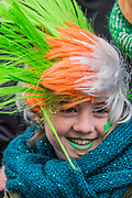 People in many types of green hats/wigs are well wrapped up against the cold as they watch the parade go by -  the London St Patrick's Day parade from Piccadilly to Trafalgar Square.
