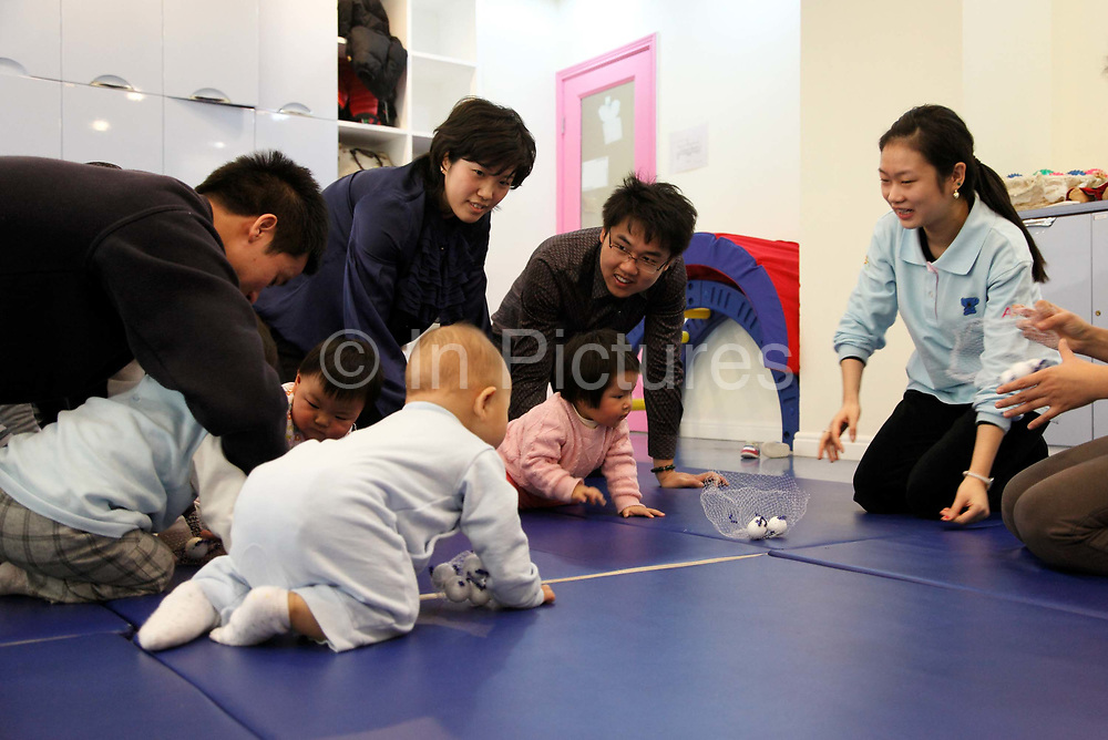 Parents play with their kids during a class for infants at a private school in Shanghai, China on 22 November 2009.  Cities such as Shanghai are now encouraging only-child couples to have 2 children instead of one as the city increasingly feels the pressure from it's rapidly graying society.