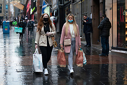 Glasgow, Scotland, UK. 11 December 2020. Covid-19 lockdown level 4 restrictions are lifted in Glasgow. Non essential businesses such as shops and restaurants can reopen from today. Pictured ; Shoppers with shopping bags out on the streets of Glasgow as shops re-opened.  Iain Masterton/Alamy Live News