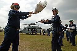 US navy personnel load a sea hawk helicopter with vital supplies for delivery to remote communities on the west coast of Aceh heavily hit by the tsunami of Dec 26th