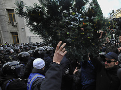 March 23, 2019 - Kiev, Ukraine - Activists of the Ukrainian far-right party National Corps are seen throwing wreath flowers next to the riot police officers standing on guard during the protest..Demonstrators demand punishment of high officials suspected of corruption in the defence complex of Ukraine. (Credit Image: © Sergei Chuzavkov/SOPA Images via ZUMA Wire)