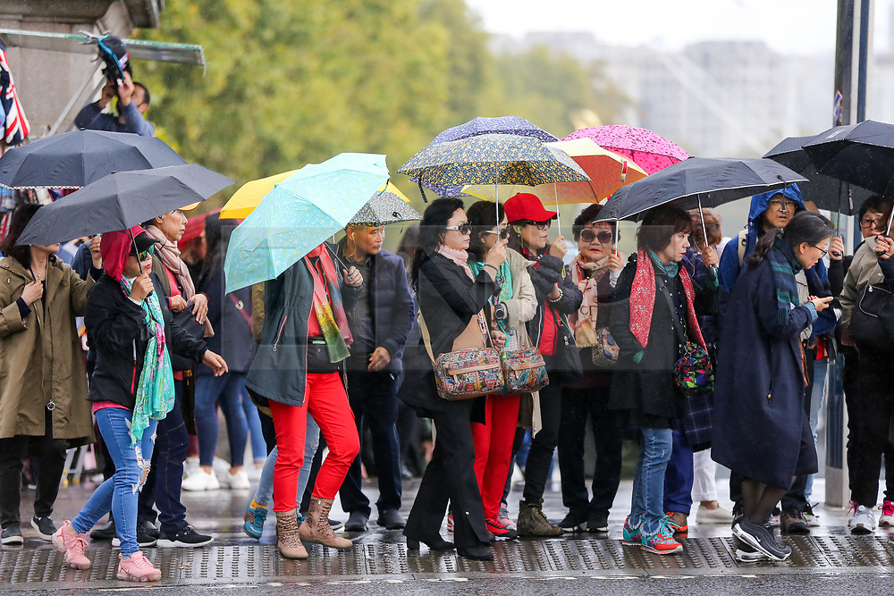 © Licensed to London News Pictures. 16/10/2019. London, UK. Tourists shelter from rain underneath umbrellas in Westminster, London. According to the Met Office more rain is forecasted for the next few days. Photo credit: Dinendra Haria/LNP