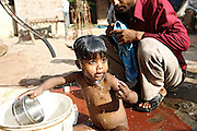 Amnoor, a 5-year-old boy from Simlana village, pop.4000, Saharanpur District, Uttar Pradesh, India, is being washed by his father using contaminated water delivered by their private hand-pump, on Sunday, Mar. 30, 2008. Amnoor was diagnosed a nervous damage due to the long-term effects of consuming unsafe water at the age of three. Before that he even used to run and was very healthy. Now, his reality is a semi-paralysis to both his left arm and leg. The family, whose only breadwinner is Vinod, 35, an agricultural labour, had to incur in a Rs 30000 (USD 600) expense for Amnoor's first treatment at the PGA Hospital in Chandigarth, Punjab, and in more than Rs 1000 (USD 12) a month for the cost of his medicines. With an average daily wage of Rs 50-60 and two more children to provide for, Vinod is facing a dire economic situation.