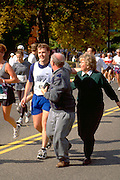 Mother and Father age 55 cheering on son age 22 running in Twin Cities Marathon.  St Paul  Minnesota USA