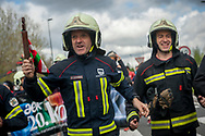 """Firefighters carry the baton while running on the 20th Korrika.  Irun (Basque Country). April 4, 2017. The """"Korrika"""" is a relay course, with a wooden baton that passes from hand to hand without interruption, organised every two years in a bid to promote the basque language. The Korrika runs over 11 days and 10 nights, crossing many Basque villages and cities. This year was the 20th edition and run more than 2500 Kilometres. Some people consider it an honour to carry the baton with the symbol of the Basques, """"buying"""" kilometres to support Basque language teaching. (Gari Garaialde / Bostok Photo)"""