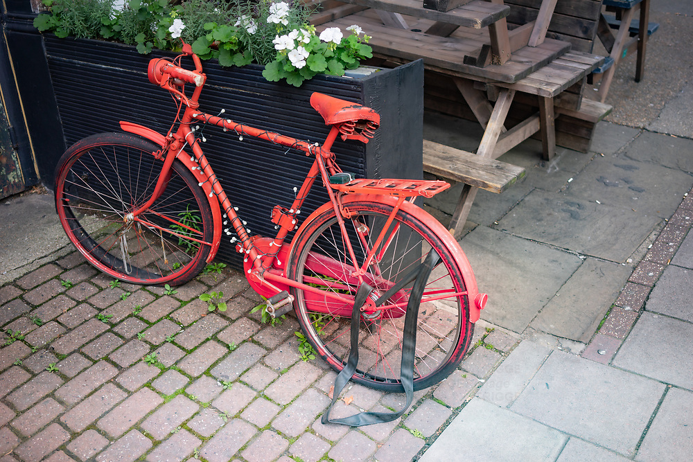 A red bicycle with lights on the street in Dulwich south London