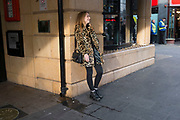 Girl wearing a leopard print fur coat smoking a cigarette while she waits in Leicester Square in London, England, United Kingdom. Her stytlish look blending in with the colour of her surroundings almost camouflage in the evening light.