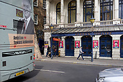 A bus with a rear ad promoting ambition and achievement passes the stars appearing in the Garrick Theatre's current musical 'Rip It Up', on 29th April 2019, in London, England.