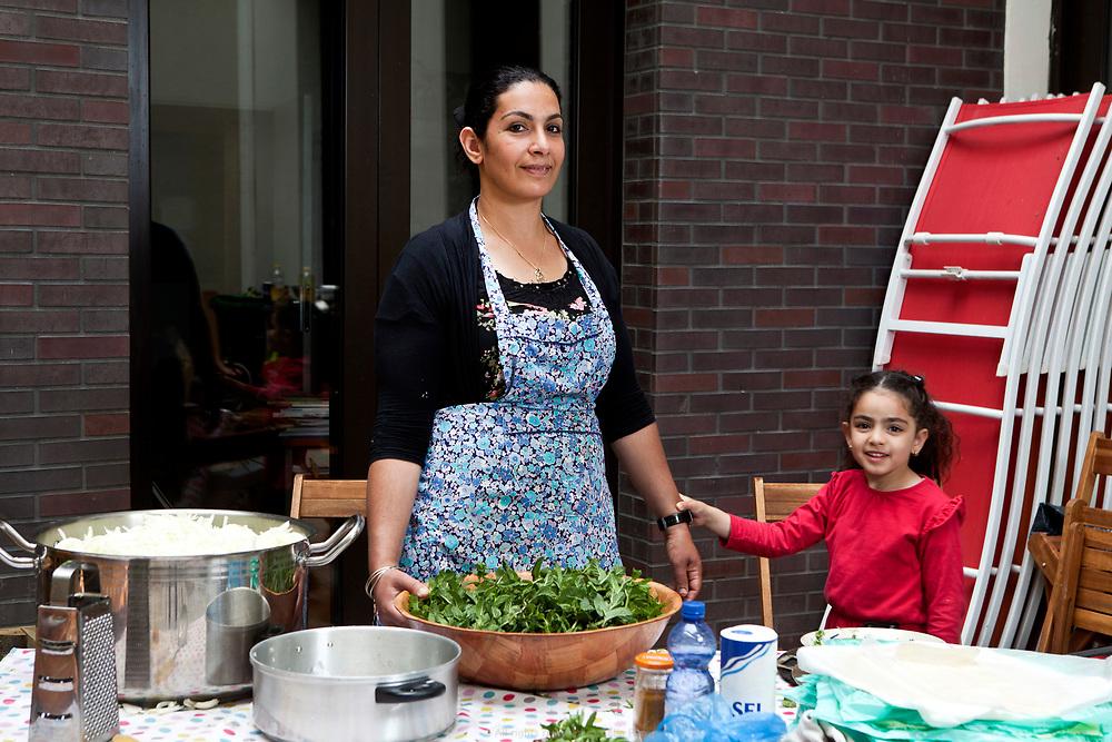 Naïma et ses filles participent à la préparation du repas de la fête annuelle de la Goutte d'Or dans les cuisines de l'association Accueil Goute d'Or.