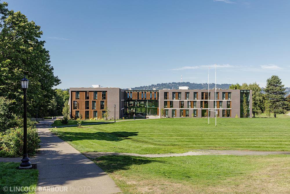 Trillium Residence Hall from a walkway showing the rugby field in the foreground and beautiful blue skies overhead.