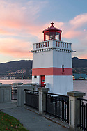 Sunset light on clouds with the Brockton Point Lighthouse  (built in 1914) along the Stanley Park seawall.  Photographed from Brockton Point at Stanley Park in Vancouver, British Columbia, Canada