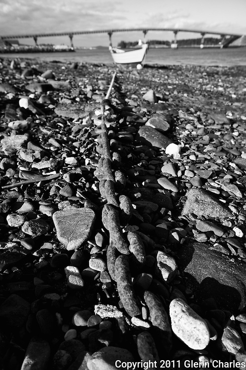 Rusted chain and anchor hold dory at low tide
