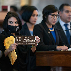 The Texas House debating SB 7 late into the night  a controversial omnibus elections bill that would make changes to the way Texas elections are held. State Rep. Ana-Maria Ramos, D-Richardson, holds a racist sign from 1929 while Rep. Jessica Gonzalez, D-Houston talks from the front mic.