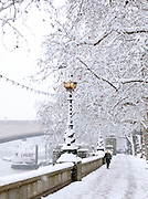 A woman walks along the south bank of the River Thames in the snow, London, UK
