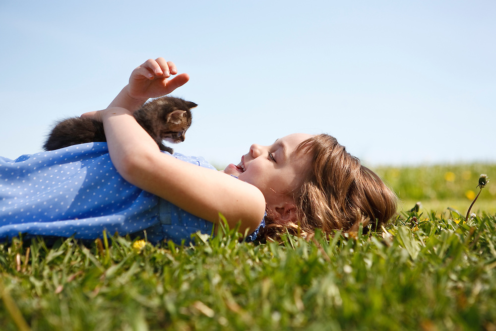 Girl 4-5 years lying on grass smiling at kitten resting on her stomach