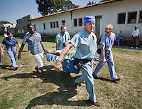 Jacksonville orthopedic surgeon John Lovejoy, Sr. helps carry a patient flown into Milot, Haiti, for treatment at Hospital Sacre Coeur February 13, 2010.  Lovejoy is leading a team of 22 to provide medical relief through an organization called Crudem.
