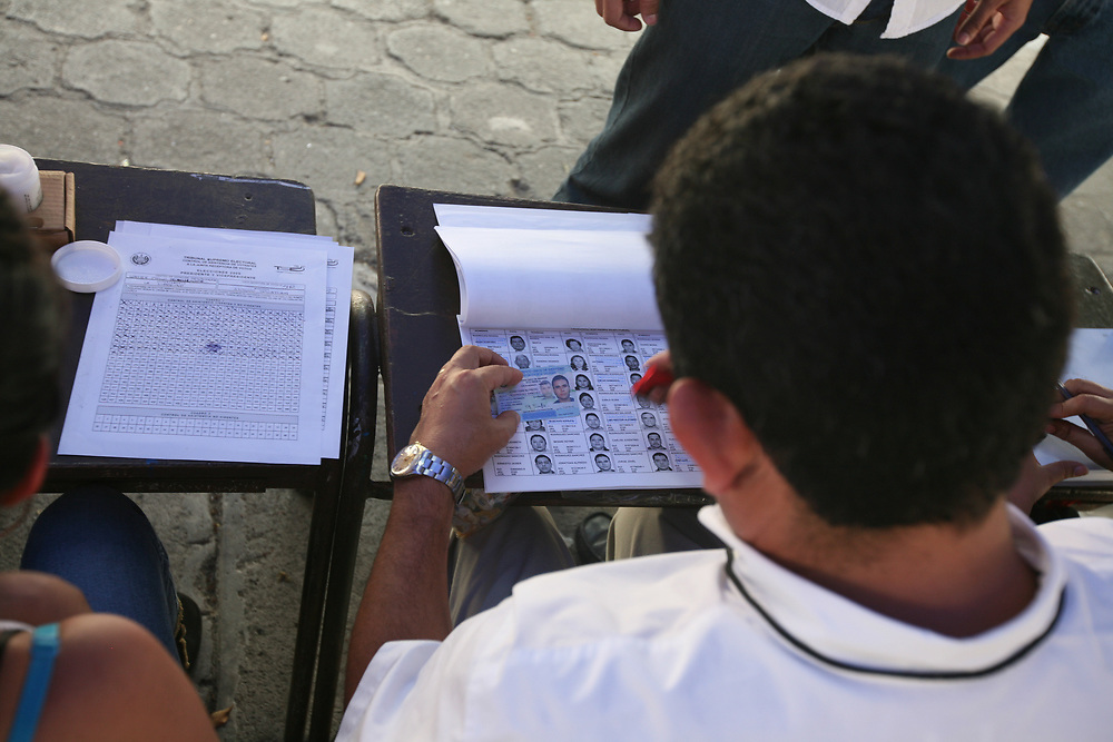 an invigilator checeds a voters identity against the voting register in San Salvador