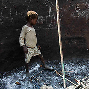 Alhadi, 6 years-old is walking through the ashes of the remains of his house which was bombed by the Sudanese government on November 8th 2012. Alhadi and his twin sister Anadi were in the house when it happened and they had to take refuge in the bunker of their garden. According to the tradition, when a house is destroyed, children have to draw on the wall either memories of the family or show what happened to it. Here, they chose to draw the rebel group (SPLA-N) pointing a gun a truck full of weapons belonging to the Sudanese government.