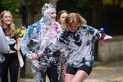 © Licensed to London News Pictures. 04/06/2021. Oxford, UK. A students at Oxford University covered in confetti, paint and foam and holding a bottle of champagne after celebrating finishing his final exams, in a tradition known as 'trashing'. Oxford University is attempting to clamp down on the tradition which sees students throwing food, confetti and drink over their classmates. Photo credit: Ben Cawthra/LNP