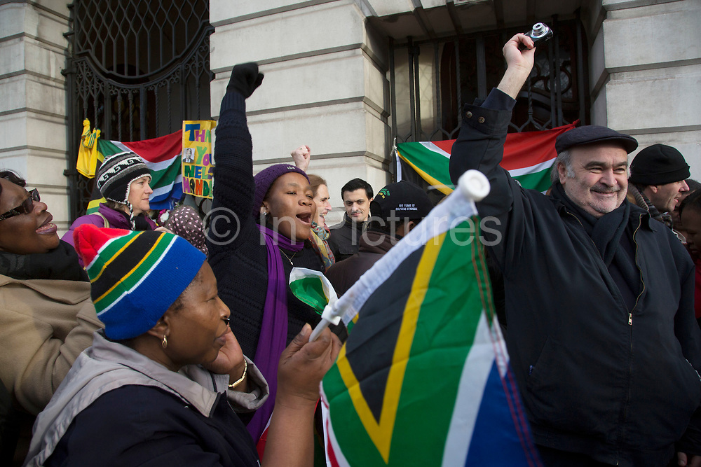 London, UK 6th December 2013: South Africans gather near to the South African Embassy, singing and dancing and waving flags to pay tribute to former South African leader and anti-apartheid ANC campaigner Nelson Mandela, who died aged 95 on 5th December 2013.