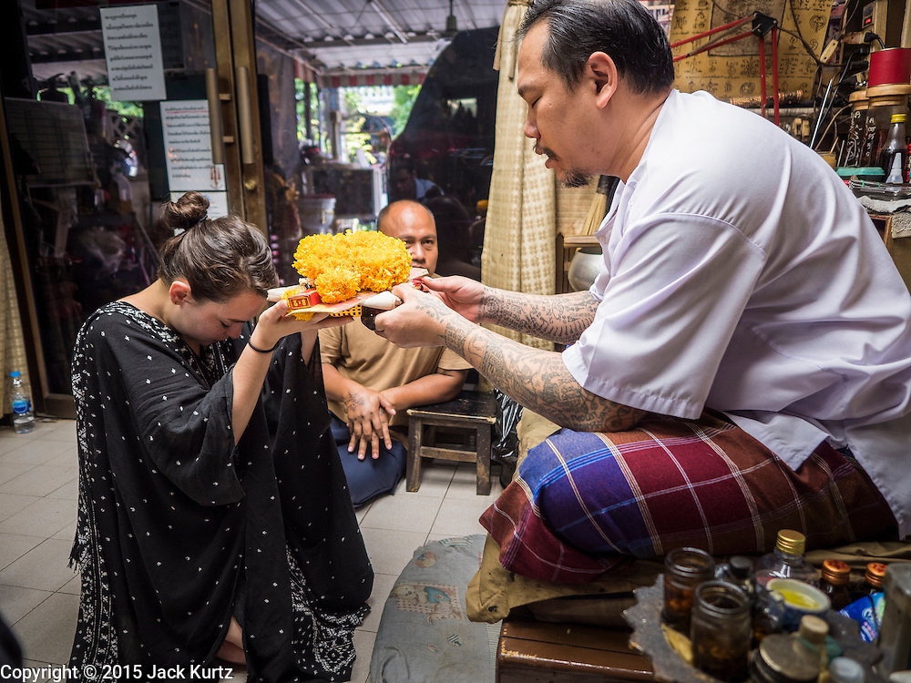 "25 MAY 2015 - BANGKOK, THAILAND: VANESSA, an American visitor to Thailand,  makes an offering to AJARN NENG ONNUT before getting a Sak Yant tattoo from him. Sak Yant (Thai for ""tattoos of mystical drawings"" sak=tattoo, yantra=mystical drawing) tattoos are popular throughout Thailand, Cambodia, Laos and Myanmar. The tattoos are believed to impart magical powers to the people who have them. People get the tattoos to address specific needs. For example, a business person would get a tattoo to make his business successful, and a soldier would get a tattoo to help him in battle. The tattoos are blessed by monks or people who have magical powers. Ajarn Neng, a revered tattoo master in Bangkok, uses stainless steel needles to tattoo, other tattoo masters use bamboo needles. The tattoos are growing in popularity with tourists, but Thai religious leaders try to discourage tattoo masters from giving tourists tattoos for ornamental reasons.       PHOTO BY JACK KURTZ"