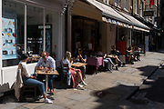 With a further 89 UK covid victims in the last 24hrs, bringing the total victims to 43,995 during the Coronavirus pandemic, pubs, restaurants and hairdressers will be able to reopen on 4th July, providing they adhere to COVID Secure guidelines. Some outdoor cafes are already open and customers in Monmouth Street in the West End sit outside in sunshine, on 2nd July 2020, in London, England.