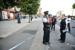 © Licensed to London News Pictures. 21/08/2018. London, UK. Police at the scene of a double shooting in Rayners Lane, Harrow, north London. Armed police are reported to be searching the area after two men were shot in broad daylight. Their condition is unknown. This follows two separate shooting incidents in London yesterday. Photo credit: Ben Cawthra/LNP