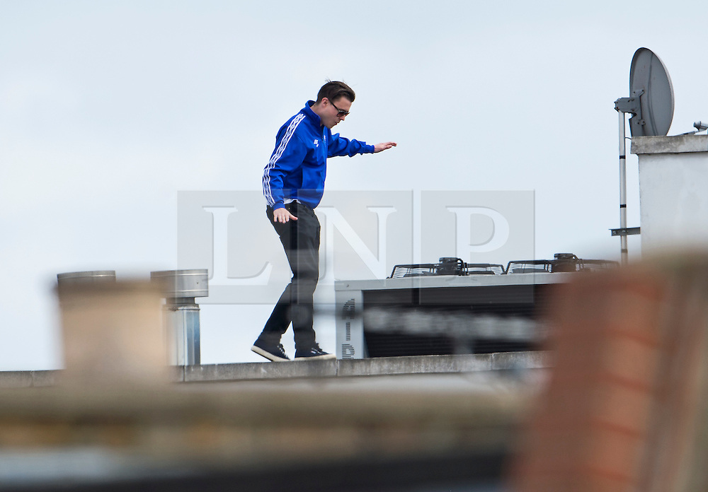© Licensed to London News Pictures. 25/05/2015. London, UK. A fan balancing on a roof top perilously in order to see the parade. The Chelsea FC first team and manager Jose Morihno parade the 2014/15 Premier League trophy and the Capital One Cup through the streets of West London in an open top bus to celebrate their seasons achievements.  Photo credit: Ben Cawthra/LNP