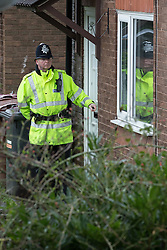 © Licensed to London News Pictures . 11/02/2014 . Blackburn , UK . A police officer pulls the front door closed at the scene . Police and forensic examiners on Emily Street in Blackburn at the scene where an eleven month old baby girl was mauled to death late last night (10th February 2014) . Photo credit : Joel Goodman/LNP