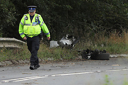 © Licensed to London News Pictures. 16/08/2020. Calne, UK. A police officer walks past vehicle debris at the scene on the A4 at Derry Hill near Calne in Wiltshire where four people have been killed in a road traffic accident in which a car is believed to have hit a house then caught fire.  Photo credit: Tim Ireland/LNP