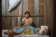 Surui, hunter with shotgun, and his family in their home at night<br /><br />An Amazonian tribal chief Almir Narayamogo, leader of 1350 Surui Indians in Rondônia, near Cacaol, Brazil, with a $100,000 bounty on his head, is fighting for the survival of his people and their forest, and using the world's modern hi-tech tools; computers, smartphones, Google Earth and digital forestry surveillance. So far their fight has been very effective, leading to a most promising and novel result. In 2013, Almir Narayamogo, led his people to be the first and unique indigenous tribe in the world to manage their own REDD+ carbon project and sell carbon credits to the industrial world. By marketing the CO2 capacity of 250 000 hectares of their virgin forest, the forty year old Surui, has ensured the preservation, as well as a future of his community. <br /><br />In 2009, the four clans and 25 Surui villages voted in favour of a total moratorium on logging and the carbon credits project. <br /><br />They still face deforestation problems, such as illegal logging, and gold mining which causes pollution of their river systems