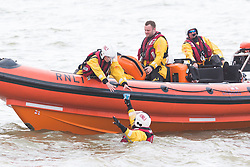 © Licensed to London News Pictures. 15/05/2016. Brighton, UK. A member of the Brighton RNLI gives ice creams to his colleagues who are patrolling the sea off Brighton. Photo credit: Hugo Michiels/LNP