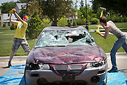 During the car smashing study break, two students prepare make some considerable impacts on the rear end of the junk car.<br /> BEN BREWER/Grinnell College